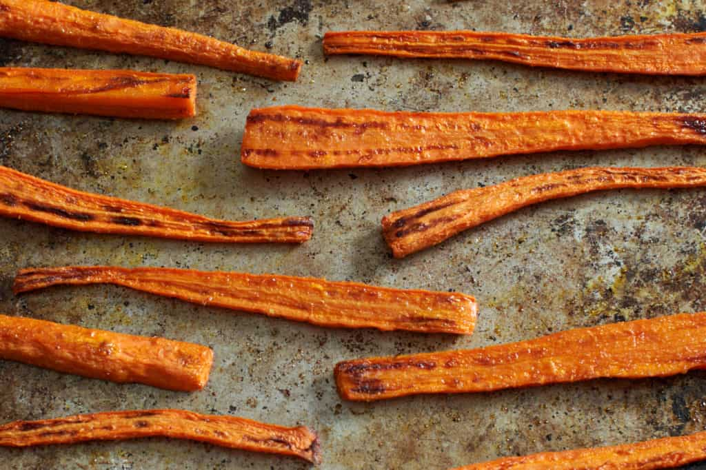Oven roasted carrots on a baking sheet.