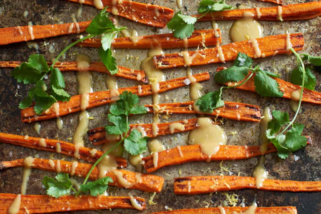 Oven roasted carrots with tahini sauce and cilantro on a baking sheet.