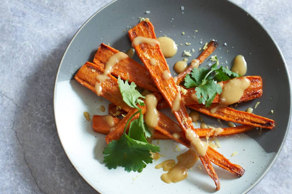 Oven roasted carrots with tahini sauce and cilantro on a gray and white plate.