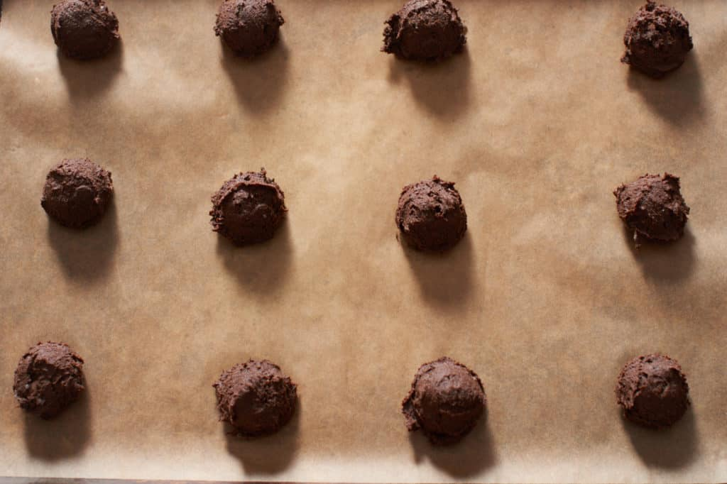 Gluten free chocolate buckwheat cookies on parchment paper ready to go into the oven.