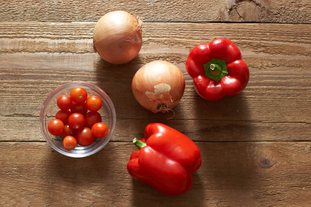 Red bell peppers, cherry tomatoes and yellow onions on a wooden surface.