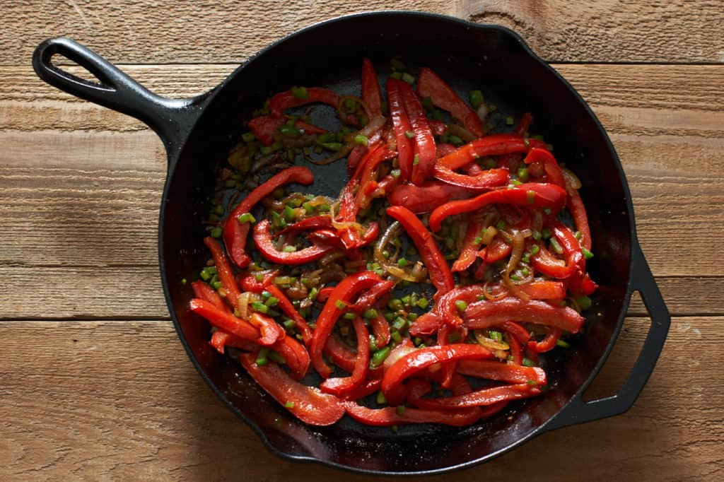A cast iron skillet with sautéed onions, red bell peppers, and jalapeños.