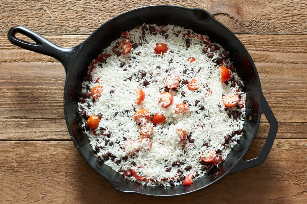 A cast iron skillet with rice, tomatoes and black beans