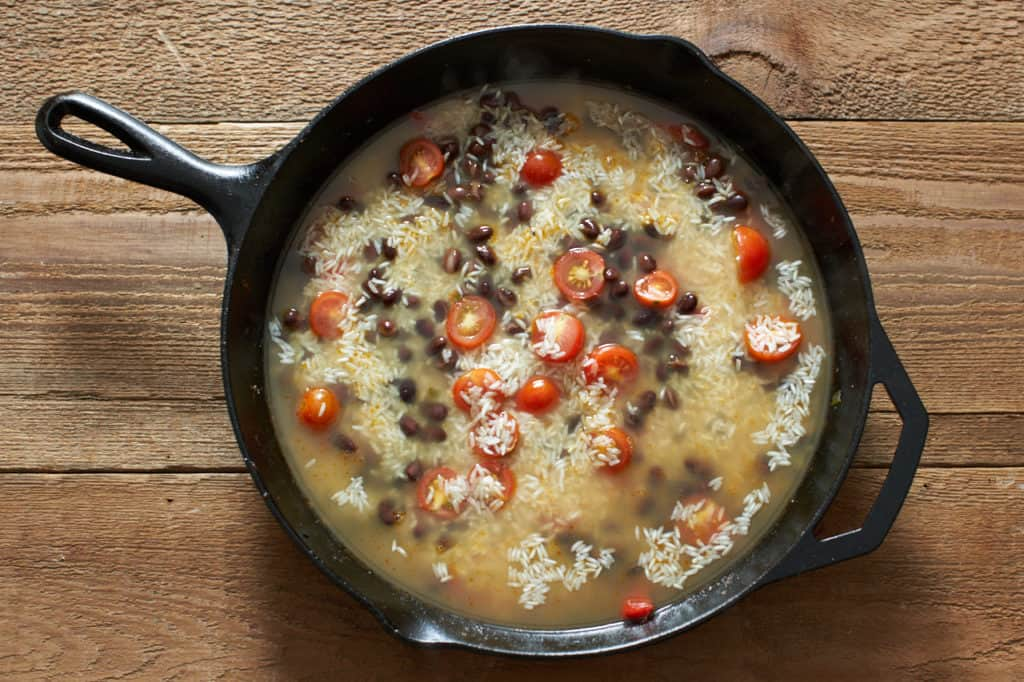 A cast iron skillet with chicken stock, rice, tomatoes and black beans