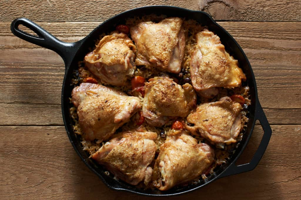 Finished one pot chicken thighs with rice and black beans in a cast iron skillet