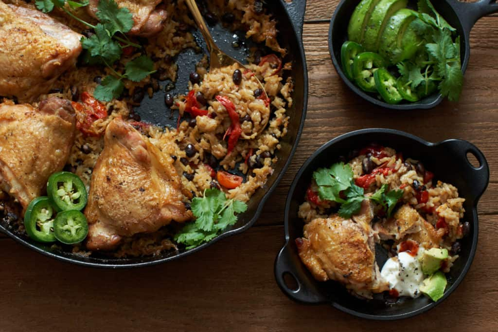 One pot chicken with rice and black beans in a cast iron skillet