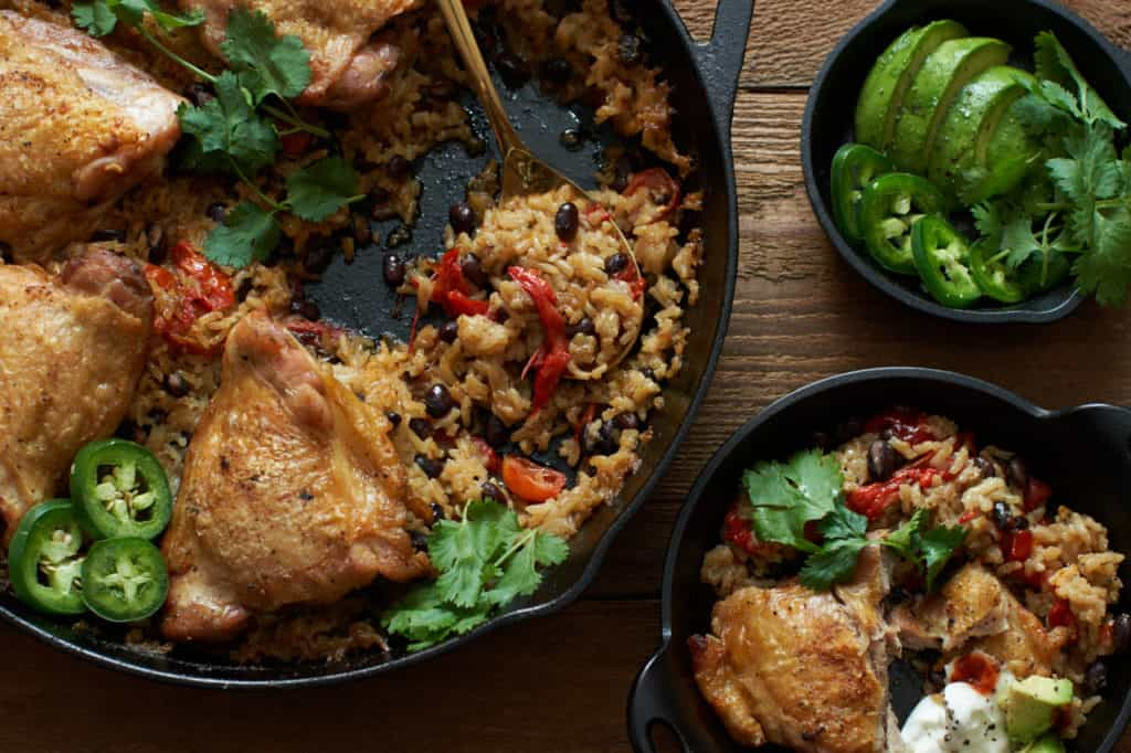 One pot chicken with rice and black beans in a skillet with a side of avocado and jalapeños