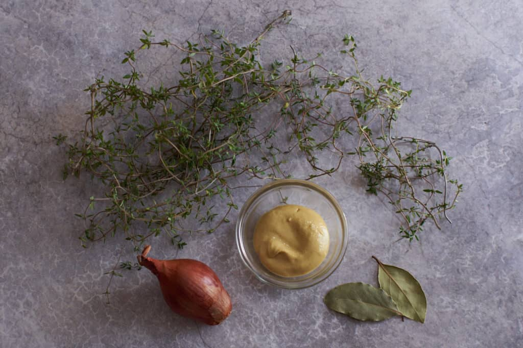 Fresh thyme, a bay leaf, a shallot, and a small bowl of dijon mustard