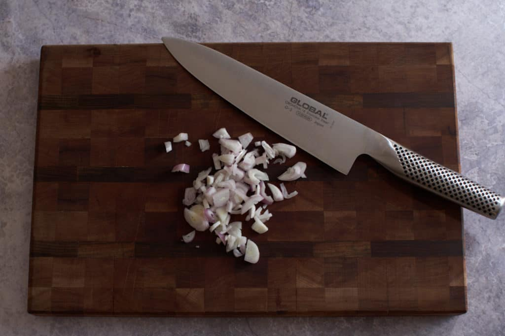 Chopped shallots and a chef's knife on a cutting board