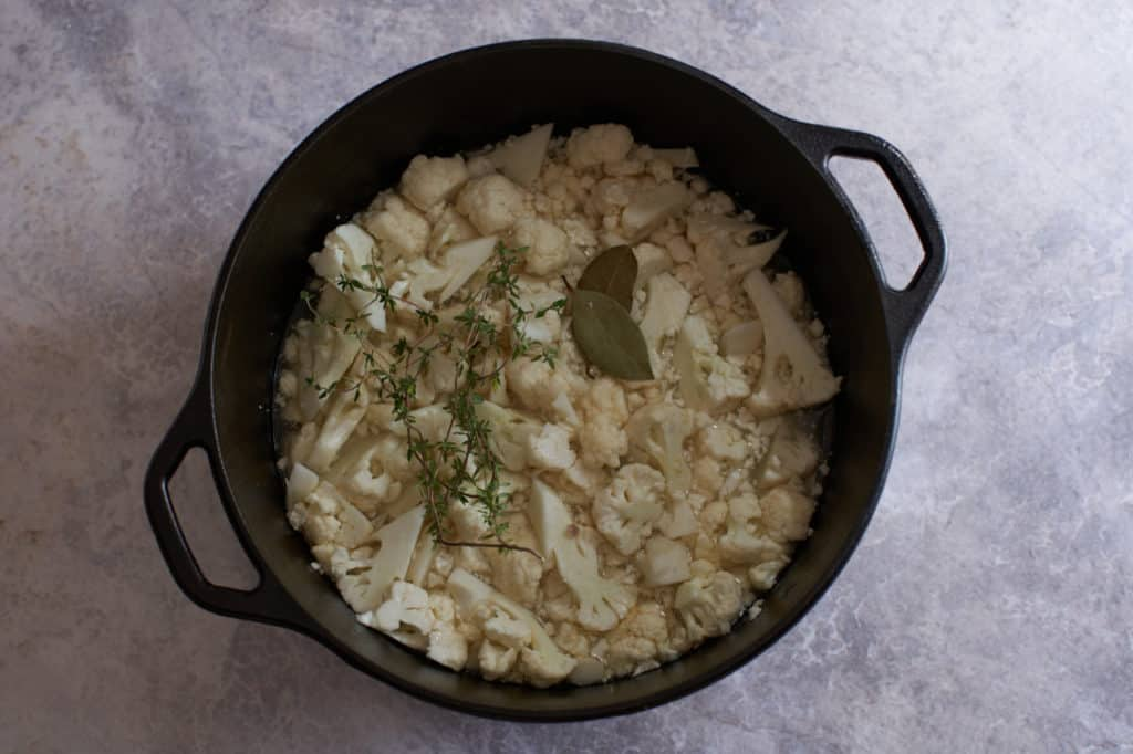 Chopped cauliflower in a pot with bay leaves and thyme