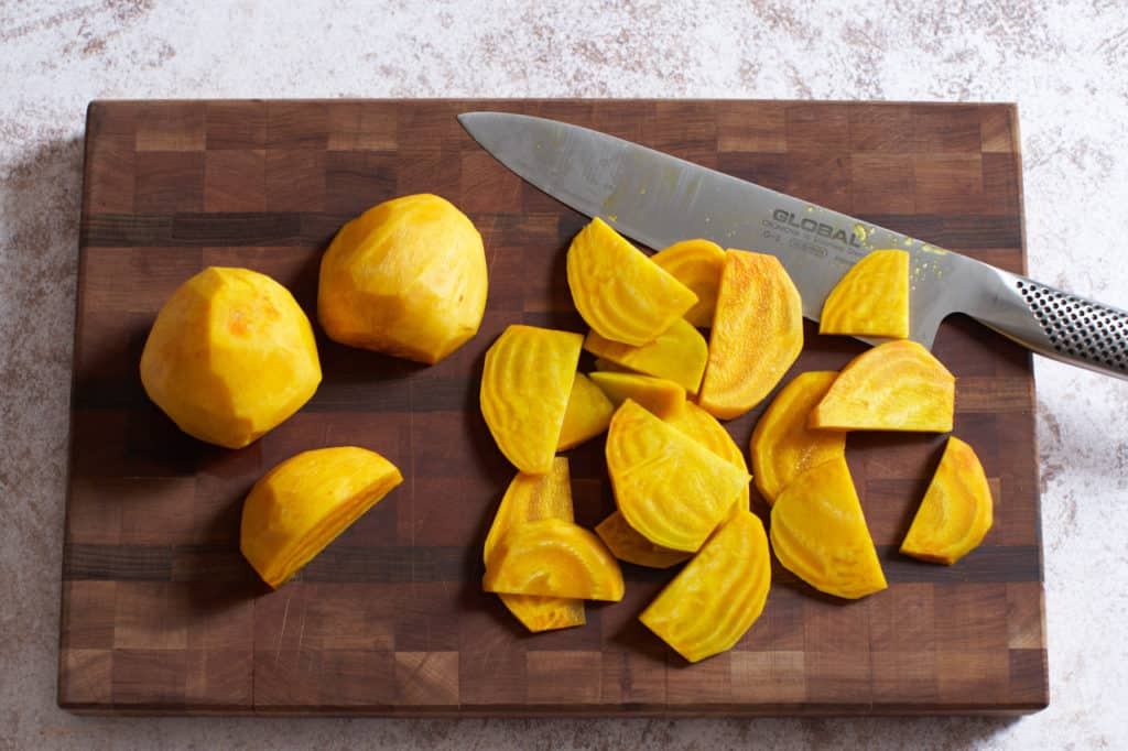 sliced golden beets and a chef's knife on a cutting board