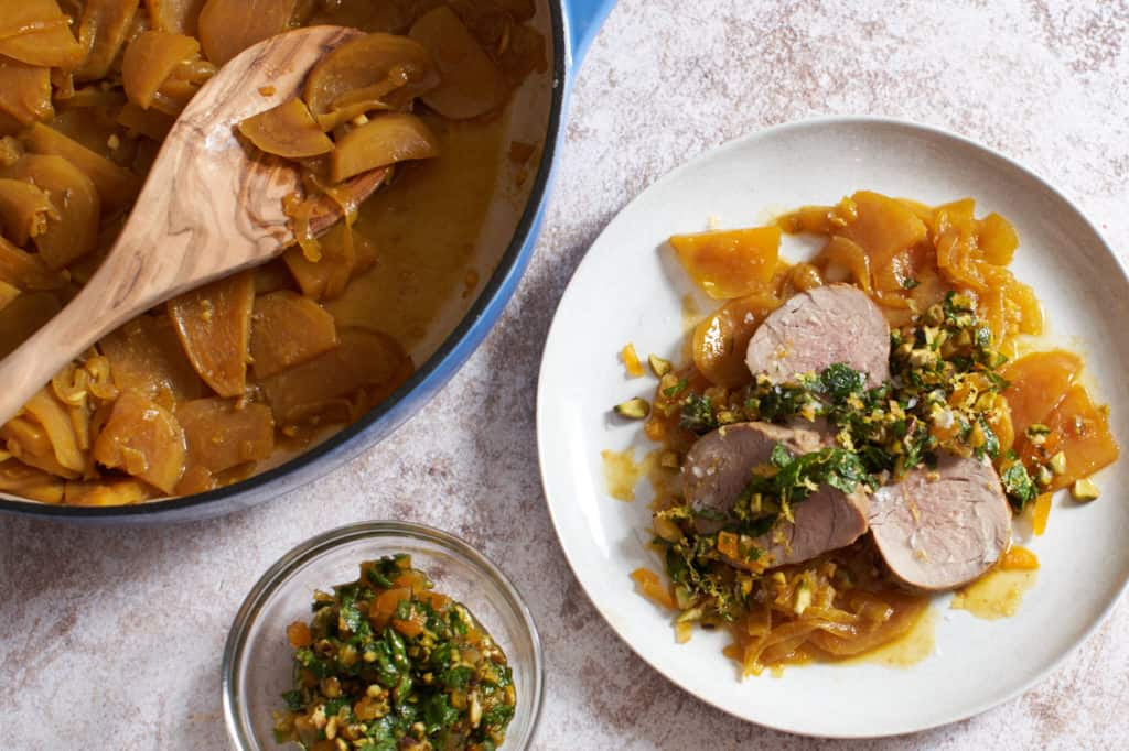 a plate of pork tenderloin with golden beets with a dish of apricot mint sauce