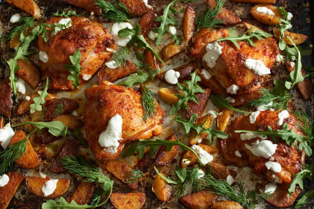 sheet pan harissa chicken thighs with potatoes, herbs and yogurt