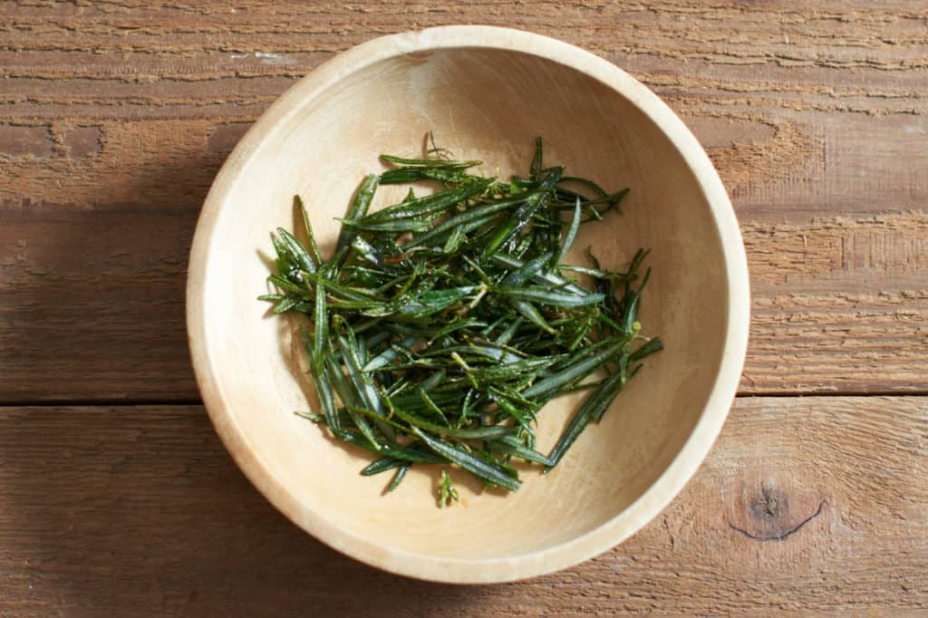 Fried rosemary fronds in a wooden bowl