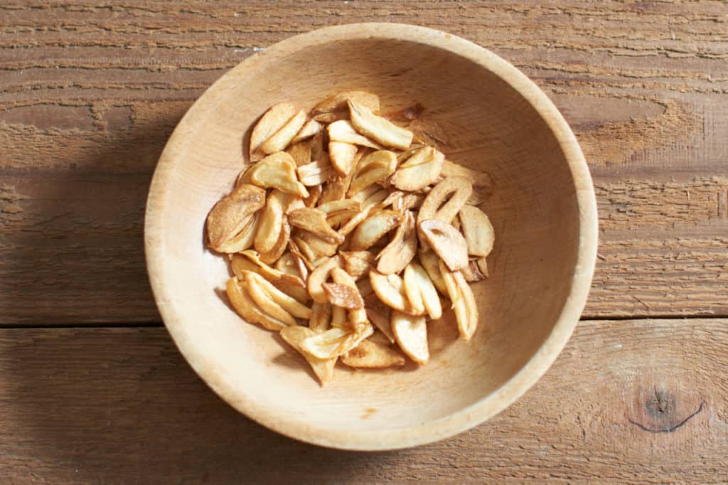 Fried garlic slices in a wooden bowl