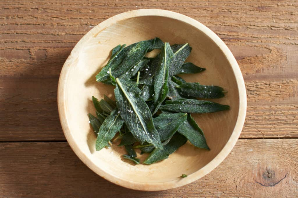 fried sage leaves in a wooden bowl