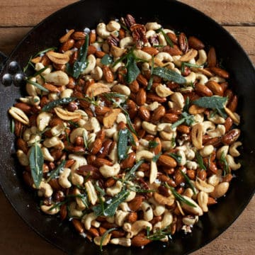 oven roasted nuts with rosemary, sage, and crispy garlic in a black skillet