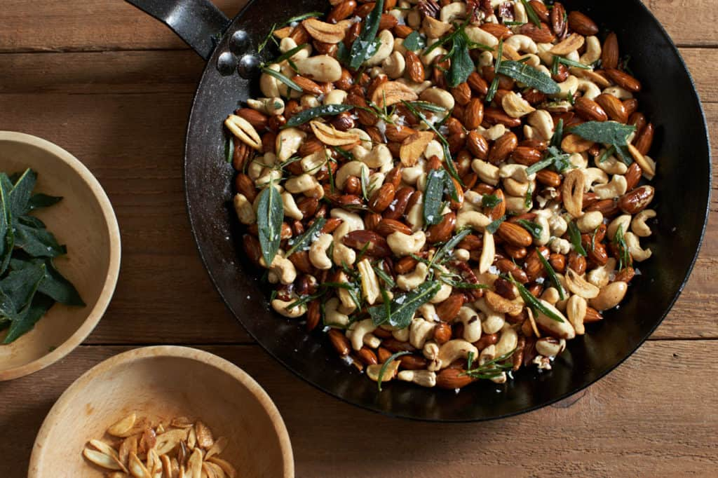 oven roasted nuts in a skillet next to two small wooden bowls with sage and garlic