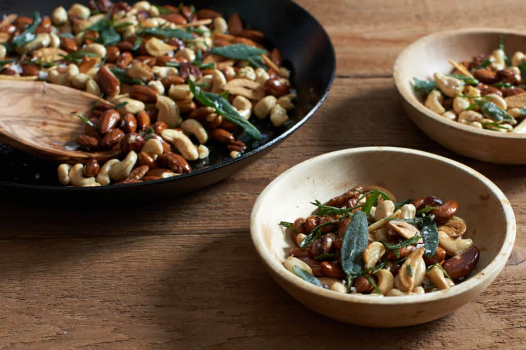 oven roasted nuts with herbs and garlic in a skillet next to two small wooden bowls filled with nuts