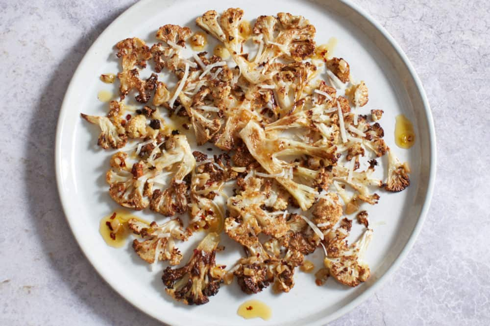 Crispy roasted cauliflower with parmesan on a white plate