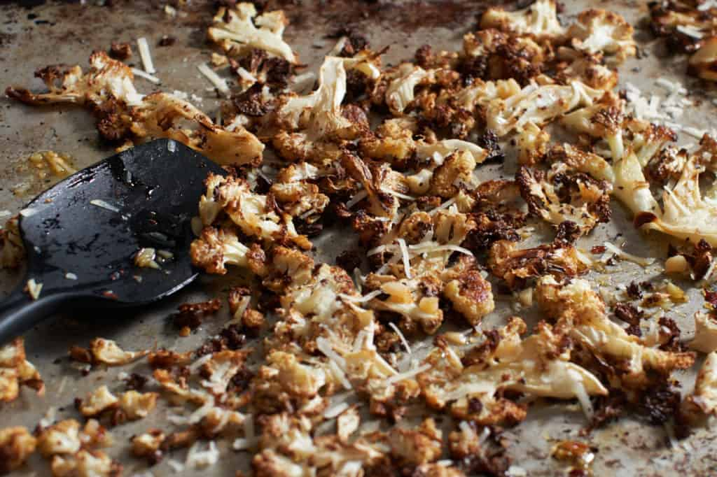 Roasted cauliflower with parmesan and garlic on a sheet pan with a black spatula