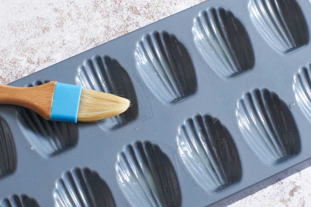 A pastry brush sits across a madeleine pan.