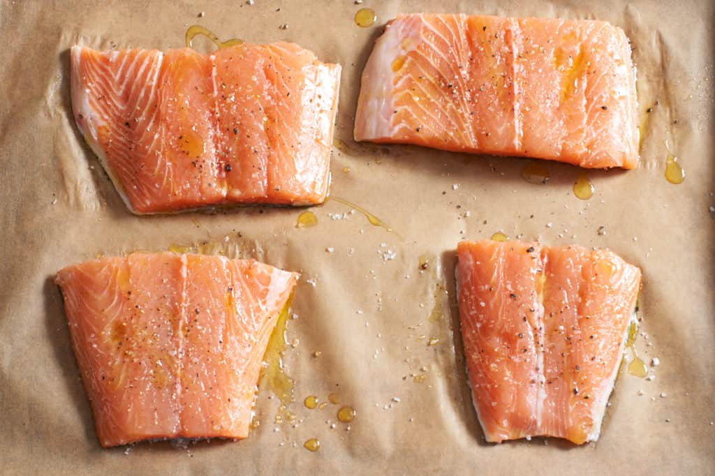 Raw salmon on parchment paper.