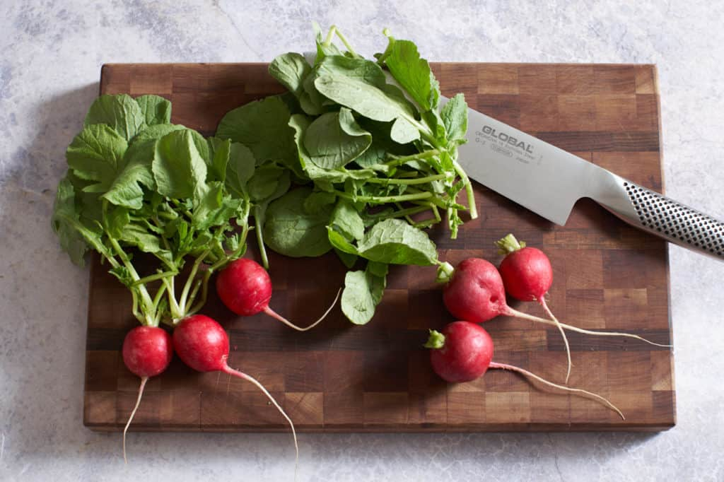 Radishes with greens and a chef's knife on a cutting board.