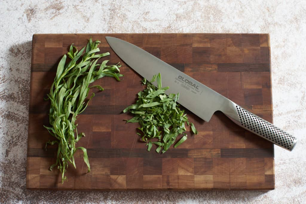 A chef's knife with chopped tarragon on a wooden cutting board.