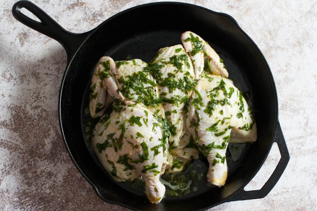 A raw chicken covered in tarragon in a cast iron skillet.