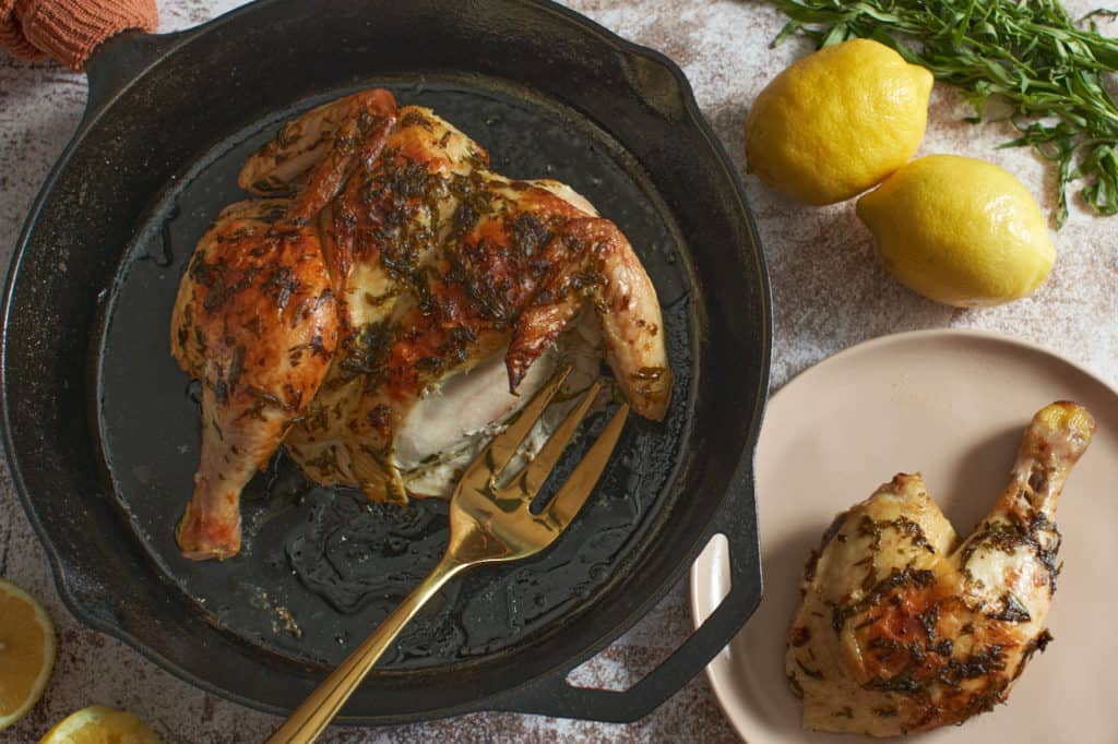Tarragon roast chicken in a cast iron skillet with a gold serving fork next to a small plate with a piece of chicken on it.