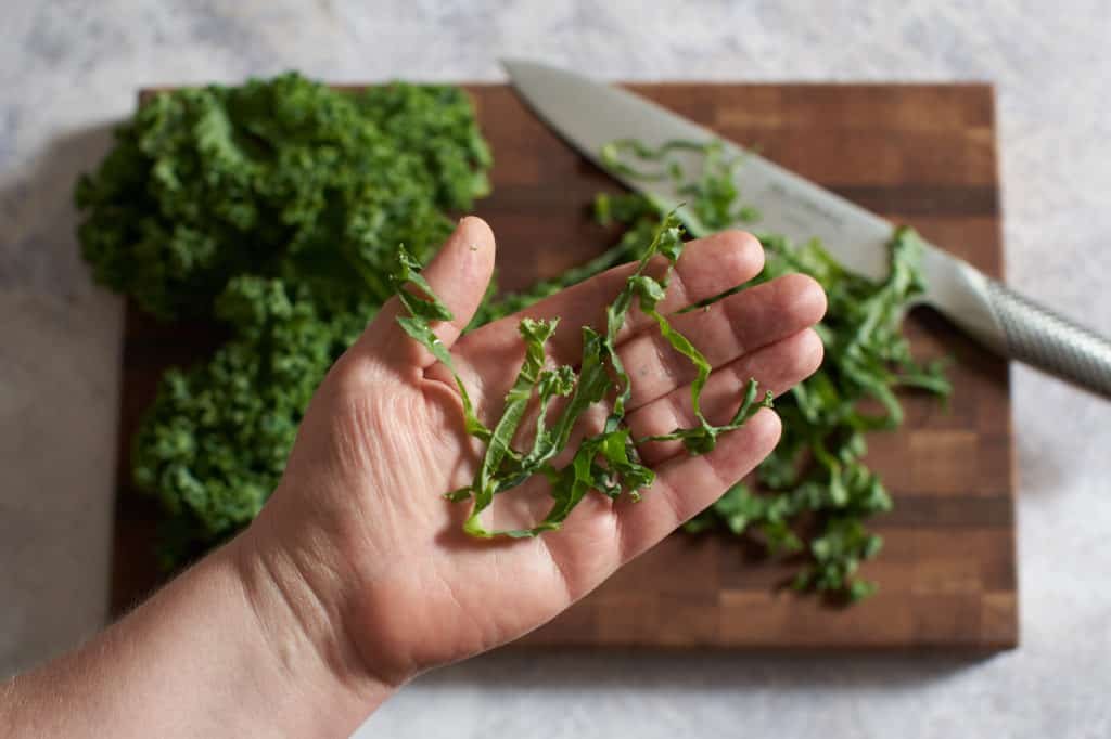 A woman's hand holding thinly sliced kale with a cutting board and knife in the background.