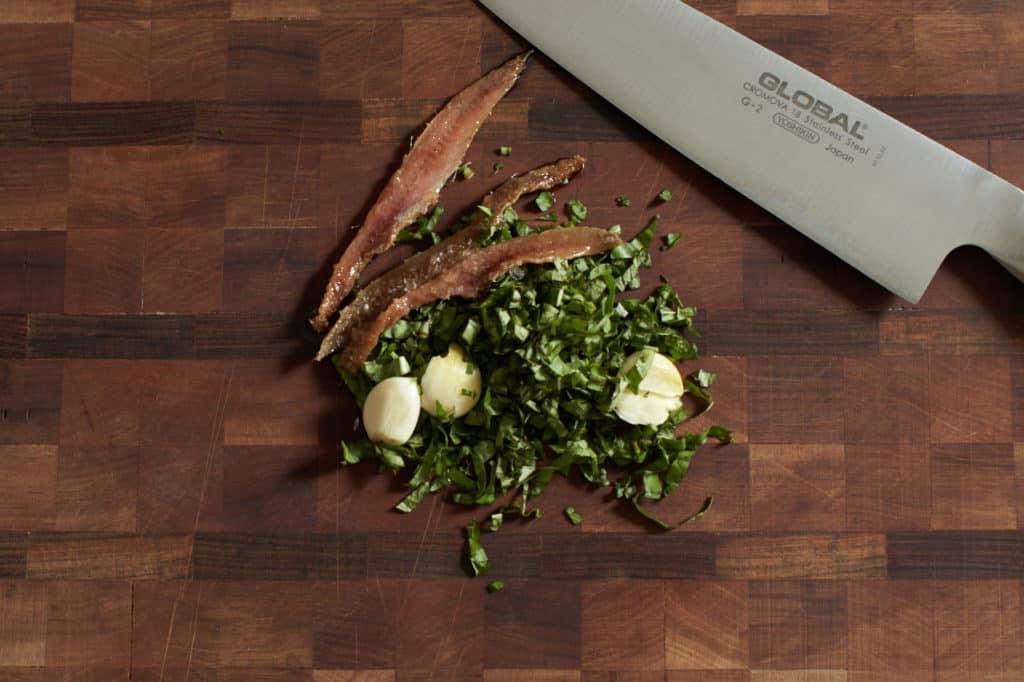 Anchovies, chopped basil, fresh garlic, and a chef's knife on a cutting board.