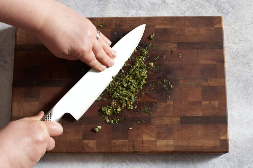A woman's hands sliding a chef's knife blade sideways through garlic and anchovies to create a paste.
