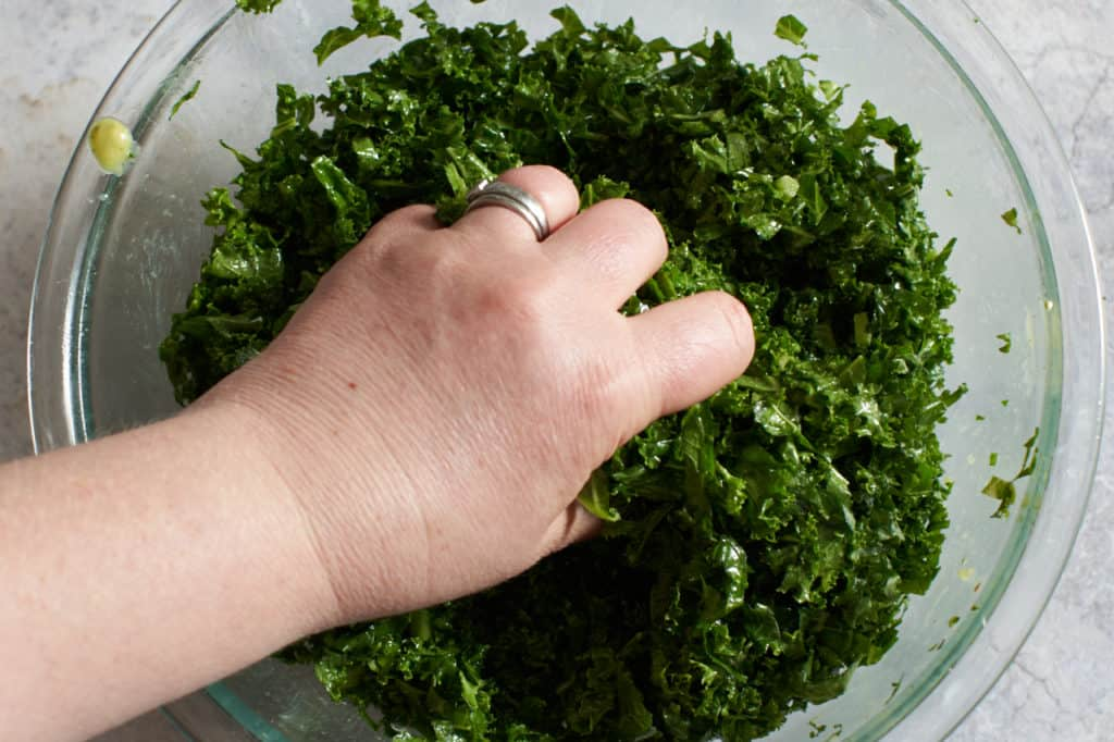 A woman's hand massaging salad dressing into kale.