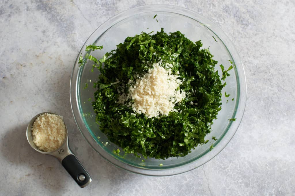 A small measuring cup of parmesan cheese next to a bowl of kale salad topped with cheese.