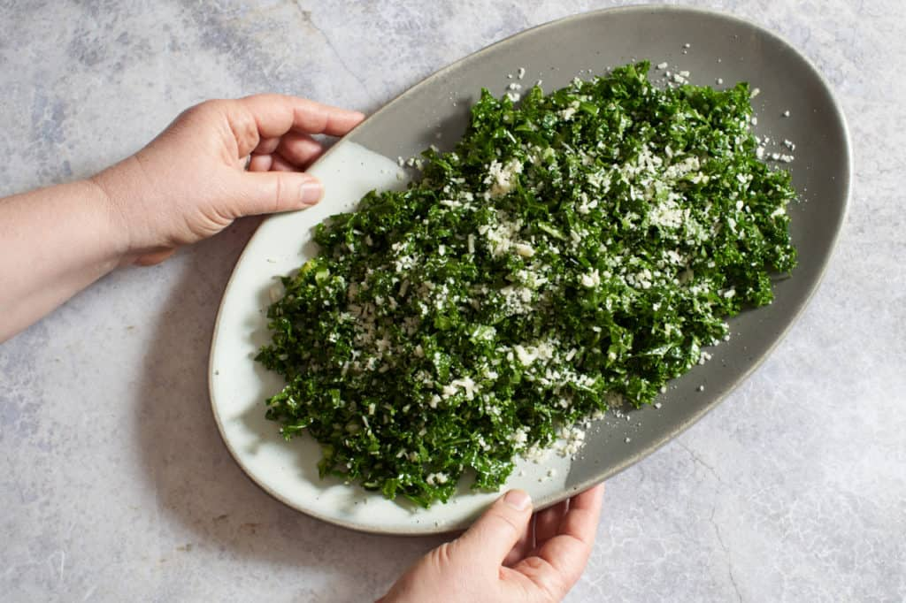 A woman's hands holding a gray and white platter of kale salad.