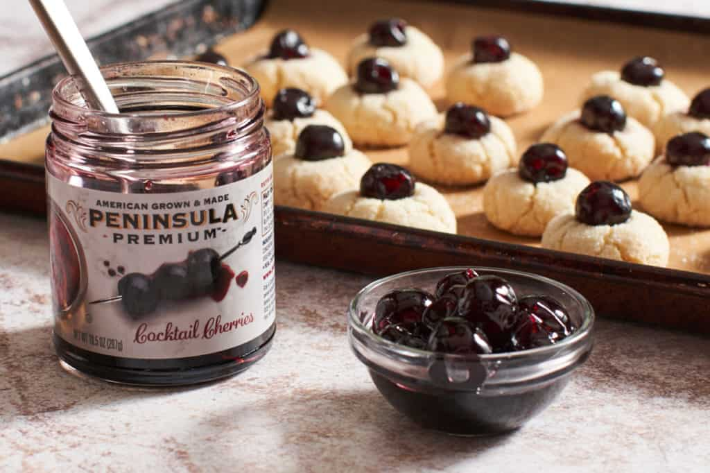 A sheet pan of amaretti cookies with a small jar and a small bowl of cherries in the foreground.