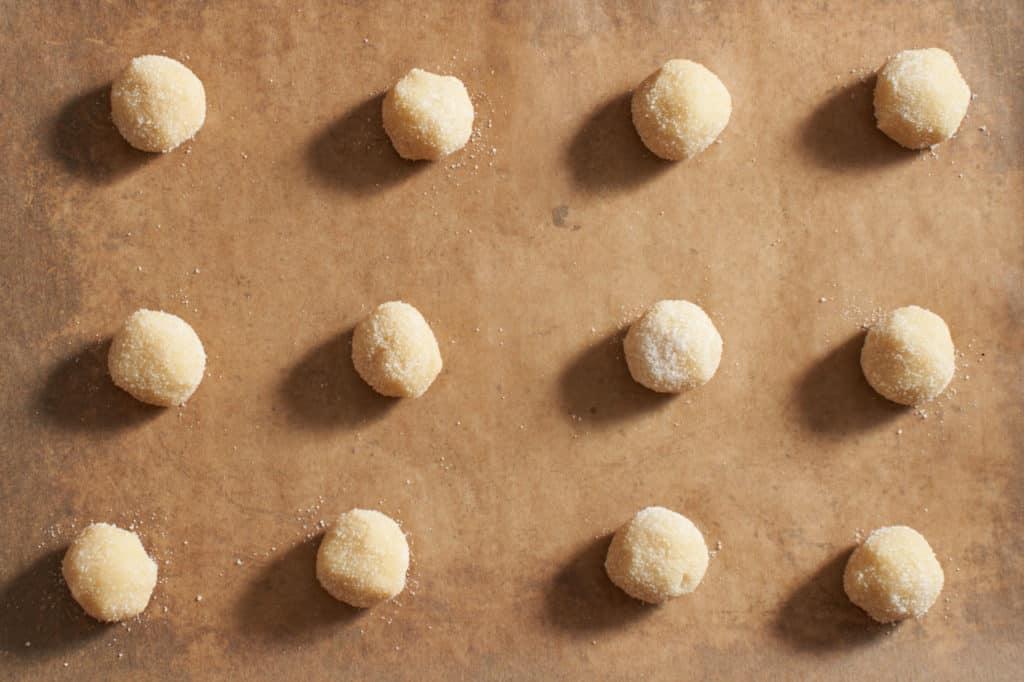 Cookie dough balls on parchment paper.