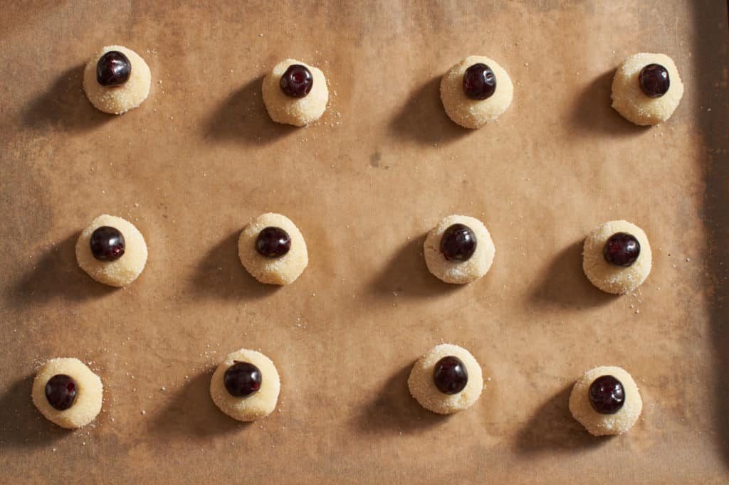 Amaretti cookie dough balls with cherries on parchment paper.