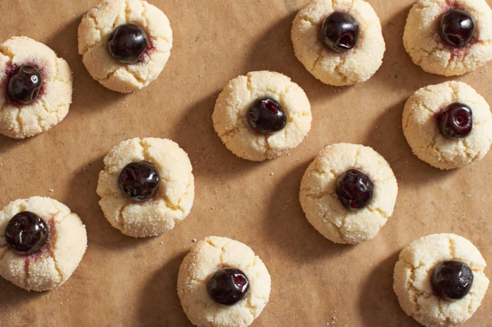 Amaretti cookies with cherries on parchment paper.