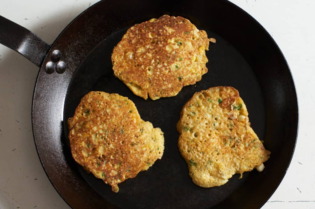 Three corn cakes in a carbon steel skillet.