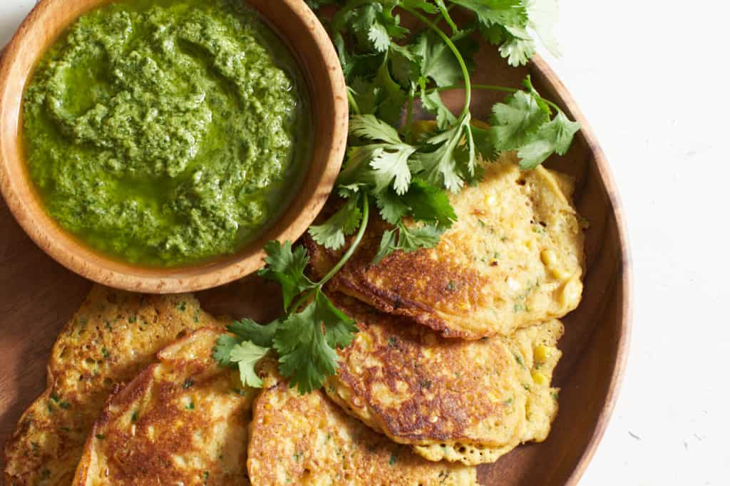 Corn cakes with a bowl of guasacaca on a wooden plate.