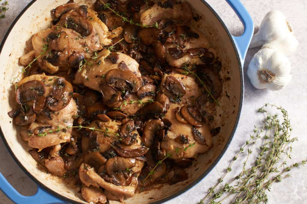 Chicken with mushrooms and white wine in a blue pan with garlic bulbs and fresh thyme on the side.