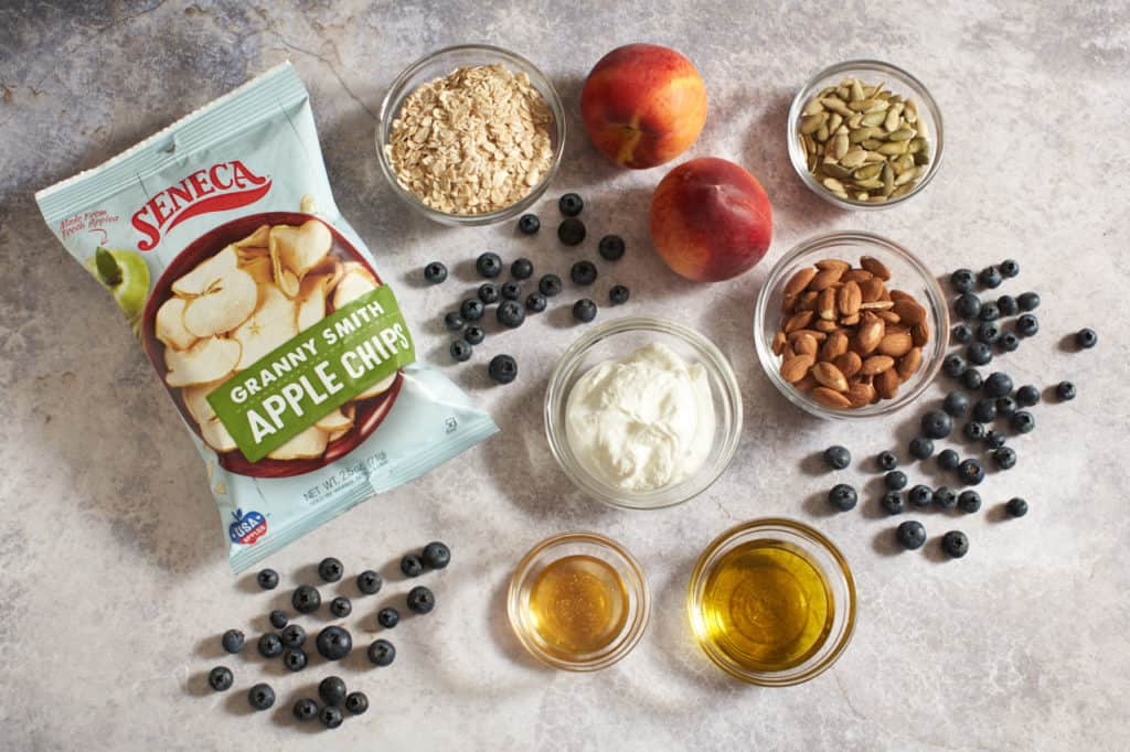 A bag of Seneca apple chips, some blueberries, peaches, and small bowls of oats, almonds, honey, yogurt and pepitas.