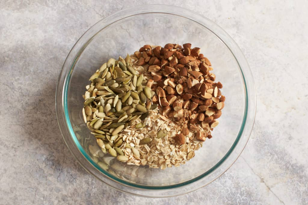 A glass bowl with oats, pumpkin seeds, and almonds.