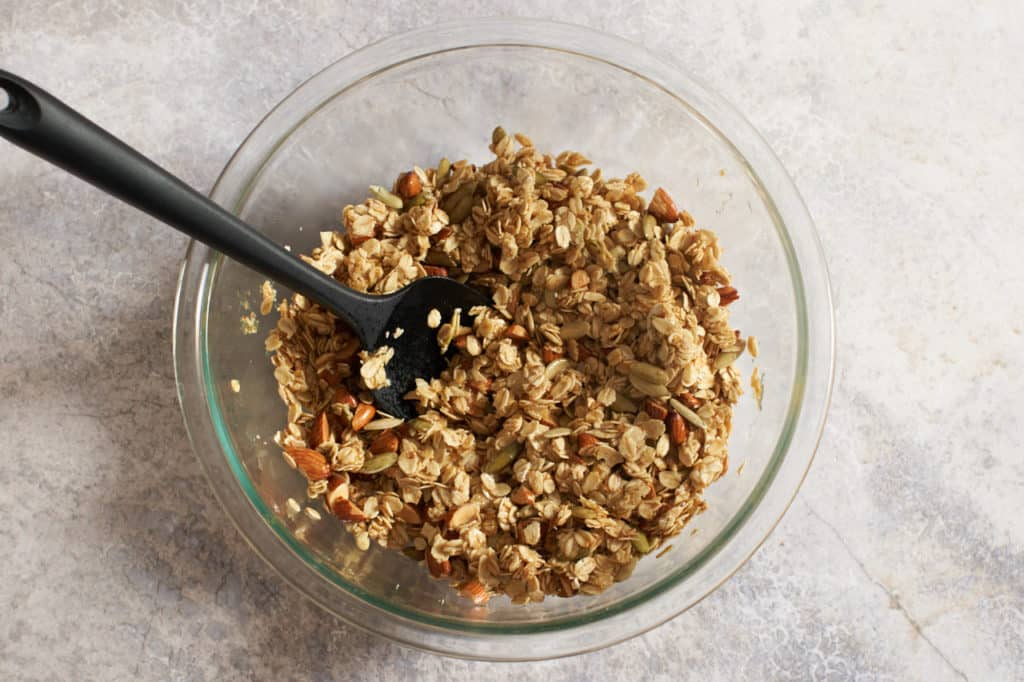 A glass bowl with a spatula and mixed granola ingredients.