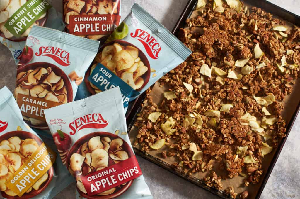 Bags of Seneca apple chips next to a sheet pan with granola.