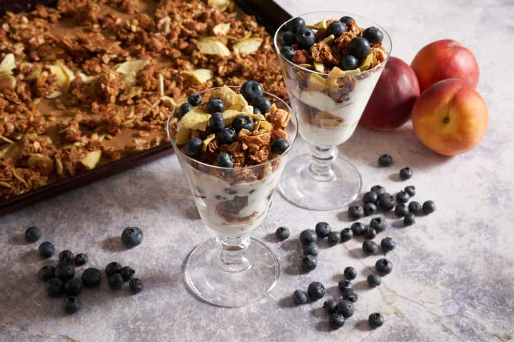 Two yogurt parfaits on a marble surface with blueberries and peaches and granola in the background..