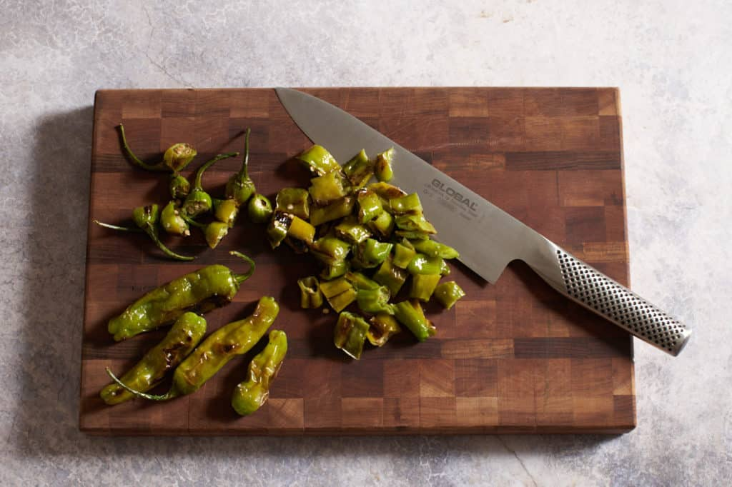 A knife on a cutting board with chopped and whole blistered shishito peppers.